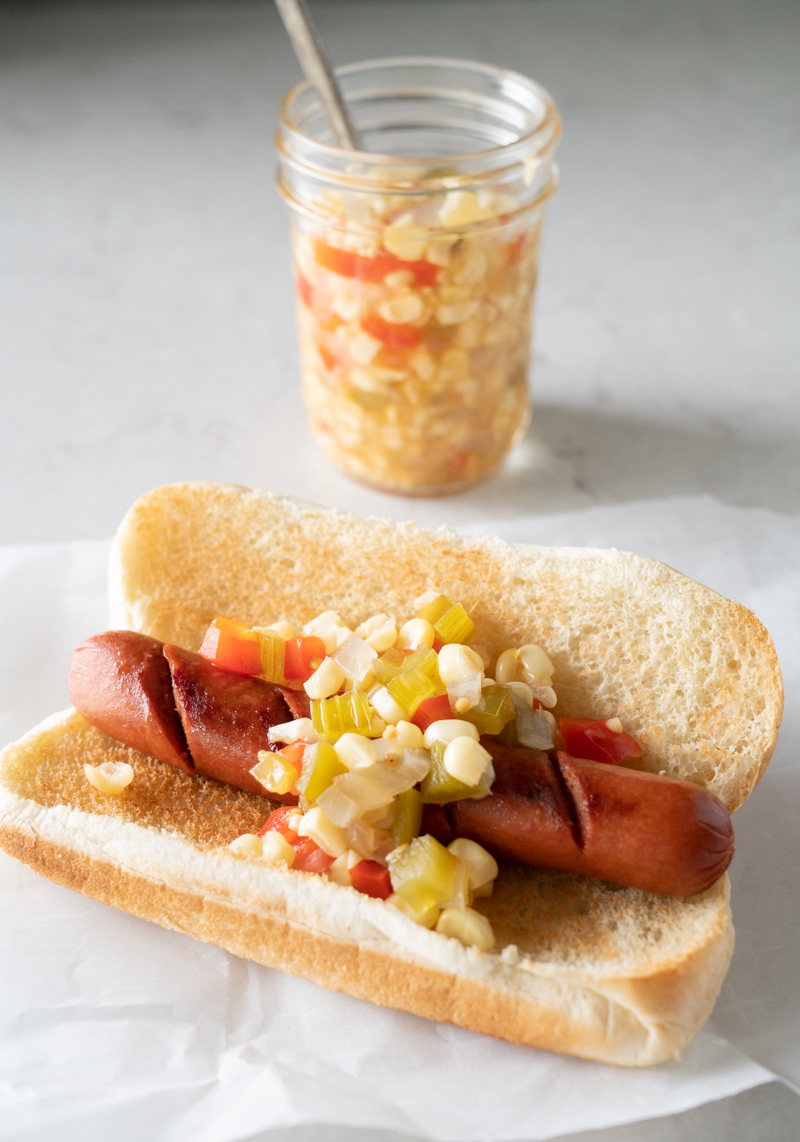 grilled hot dog in a bun with corn relish on the side. www.mountainmamacooks.com