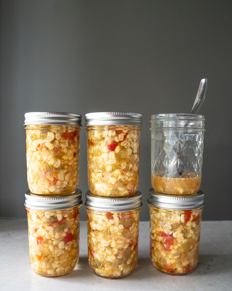 six jars of corn relish that are preserved for shelf life. One jar of corn salsa is empty. www.mountainmamacooks.com