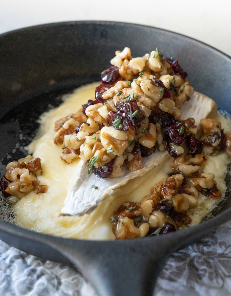 A close up image of oozing hot brie cheese topped with walnuts, dried cranberries, and local honey. www.mountainmamacooks.com