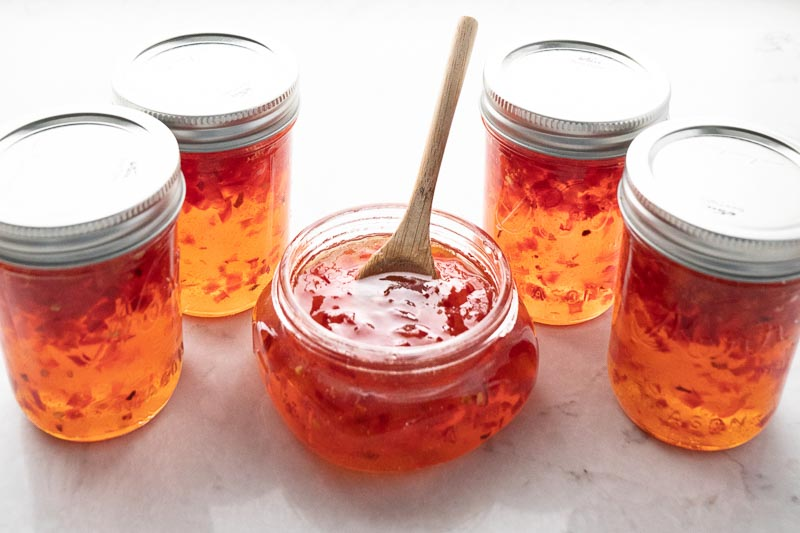 Five mason jars fill with the most gorgeous orange hued red pepper jam. The middle jar is open and has a small wooden spoon it it. www.mountainmamacooks.com
