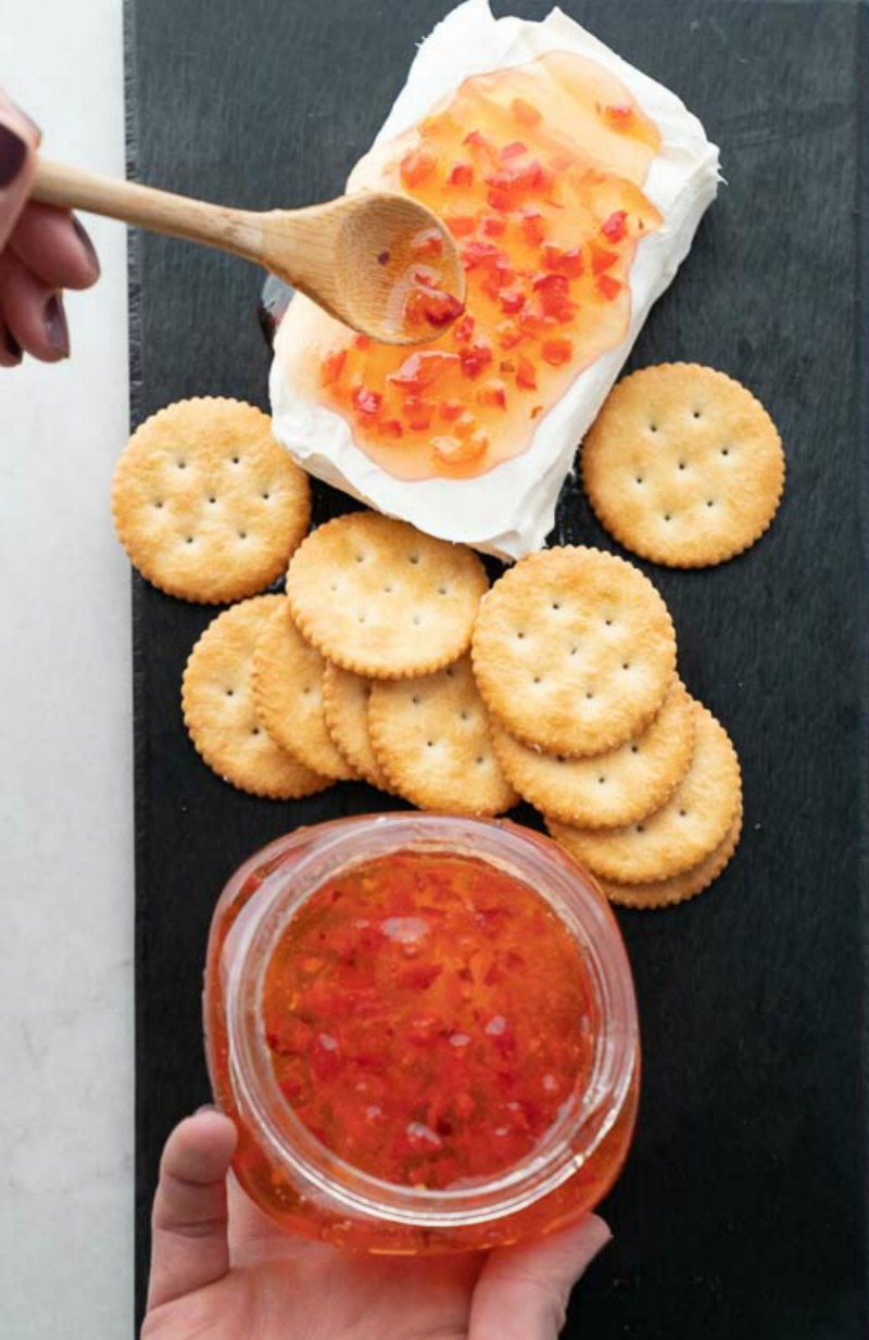 A black tray fills the image with what is the easiest appetizer ever! Cream cheese, homemade red pepper jelly, and butter crackers. Image is a woman spooning the jelly onto the cream cheese. www.mountainmamacooks.com