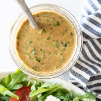 A mason jar filled with the most delicious, slightly sweet basil balsamic vinaigrette. www.mountainmamacooks.com