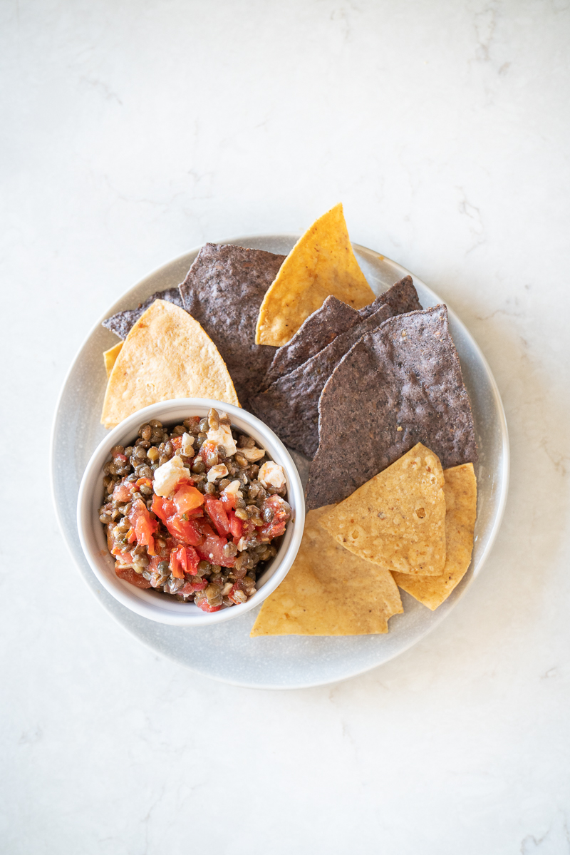 A platter of blue and yellow organic tortilla chips and an easy 3-ingredient trader joes lentil dip. www.mountainmamacooks.com