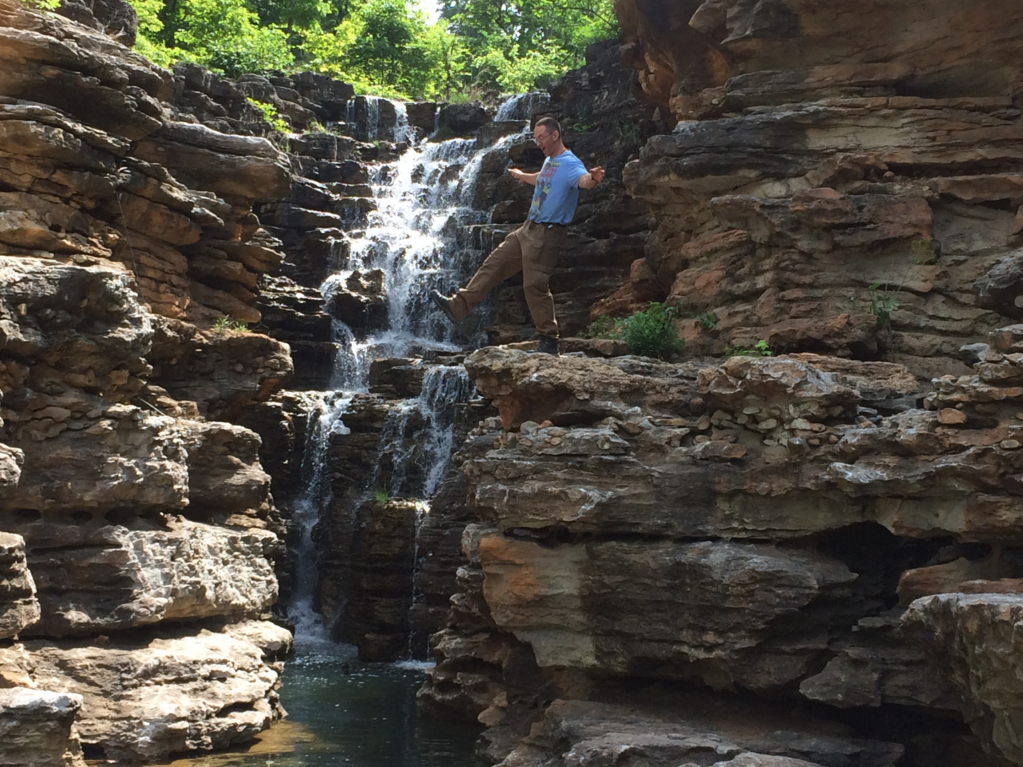 Instructor Hutch dancing on a ledge next to a waterfall