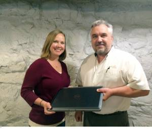 Bill Lenherr, president and CEO of Greenbrier Technologies presents Kasey Carter, executive director for Communities In Schools of Greenbrier County with the donated laptop