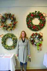 The Holiday by Design wreath and Christmas Tree auction at the Greenbrier Valley Visitors Center benefits the United Way of the Greenbrier Valley, with funds going toward local food banks and emergency heating initiatives. Here, United Way of the Greenbrier Valley Executive Director Cindy Lavender-Bowe visits the installation during the Holiday Open House (Photo by Sarah Mansheim)