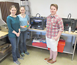 """Greenbrier East High School pre-engineering students Erin Leslie, Sarah Leslie and Taylor Lewis demonstrating the eight inch 3D printer in action. This is the very printer used to create the state's first school created and donated 3D """"Raptor"""" prosthetic hand."""
