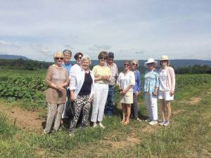 On Wednesday morning, June 24, members: Susan McKinney, guest (left); Judy Deegans, Peggy Brown, Mary Lindquist, Mary Jo Thompson, Johnny Diehl, farm manager who conducted the tour; Susan Ernst, guest; Barbara Tuckwiller, Polley Cunningham and Townley Hamilton, club president, learned of the many varities of vegetables grown from spring to fall at Eagle Rock, VA,  that are served to guests at the resort in White Sulphur Springs.