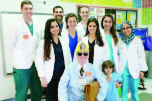 """Dr. Larry Davis (seated) was the facilitator of the eight second-year WVSOM students (future doctors) who prepared and presented """"Safety & Health"""" to the second grade class of Deborah W. Johnson at Ronceverte Elementary School. The students were: Middle Row: Sana Amad (left), Taylor Augustine, Sarah Abla, Suzanne Al-Said and Jumana Al-Deek. Back Row: Matthew Antalis (left), Umair Ahmed and Jay Alden. Standing beside Dr. Davis is Adam Al-Deek, son of Jumana Al-Deek."""