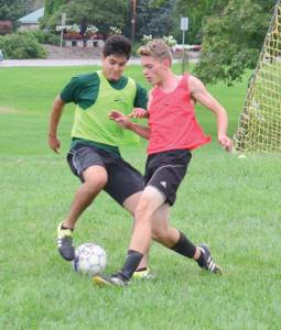 Brandon Cruz (left) and Scott Soucier are focused on the soccer ball during a practice session held this week at Greenbrier East's front field. East's first boys soccer game will be at James Monroe, Tuesday, Aug. 23, at 6 p.m. Three consecutive home games will follow on the 25th, 26th and 27th, Thursday, Friday and Saturday. (Mark Robinson photo)