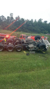 The truck overturned after truck bed became lodged