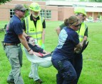 """""""CERT"""" TRAINING at DSLCC—Participating in a mock disaster recently at Dabney S. Lancaster Community College as part of the CERT (Campus Community Emergency Response Team) training were: Shane Byer (left), a member of the Covington Fire Department and a DSLCC Emergency Medical Services student, along with DSLCC staff members Michael Scott of Roanoke, Jeanette Mann of Covington and Ted Wiseman of Clifton Forge. Playing the victim was DSLCC EMS graduate Morgan Murray, who is an A-EMT and a member of the Dunlap Fire and Rescue Squad. The team was practicing transporting a patient using a blanket in lieu of a stretcher. DSLCC is one of only 13 community colleges with a CERT team."""