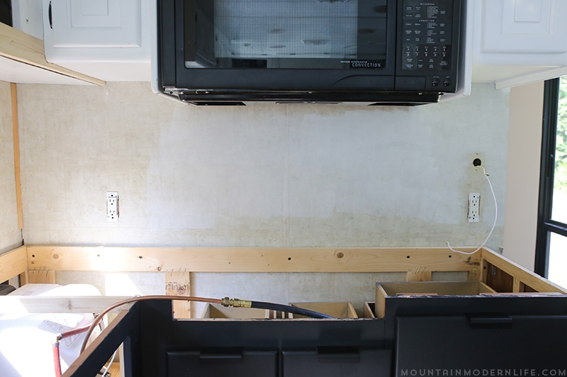 Easily install a wood planked kitchen backsplash in a RV! This is the perfect way to add rustic modern or farmhouse style to your tiny home on wheels!