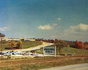 In 1962 the campus included the Administration and Academic Building on top of the hill and the new Fred B. Greear Gymnasium-Auditorium on the right. Behind the tree to the right of the sign is the other original stone building of the Poor Farm, Martha Randolph Hall.
