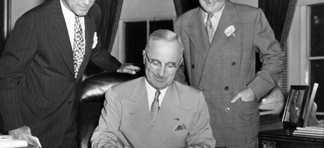 President Truman, with Sen Fulbright and Assistant Secretary Benton, signs the Surplus Property Act into law