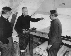 Rear Admiral Richard Byrd, center, explains a plan to fellow Operation Highjump members at their Little America IV camp. By US Navy, National Science Foundation
