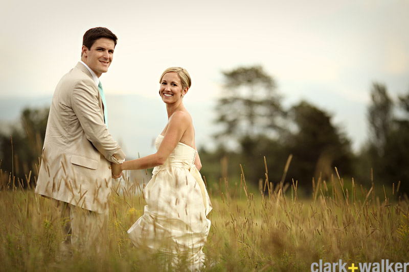 Bride and groom hold hands in a field