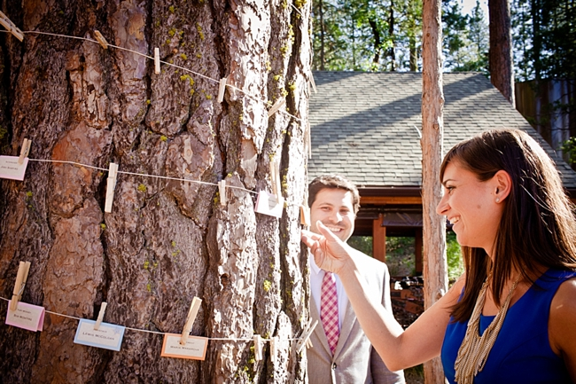 paper escort cards on twine wrapped around a tree
