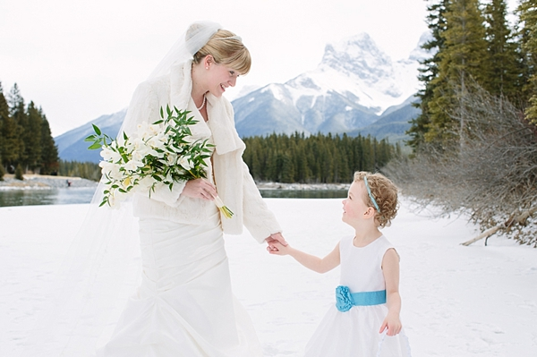 bride in the mountains with flower girl