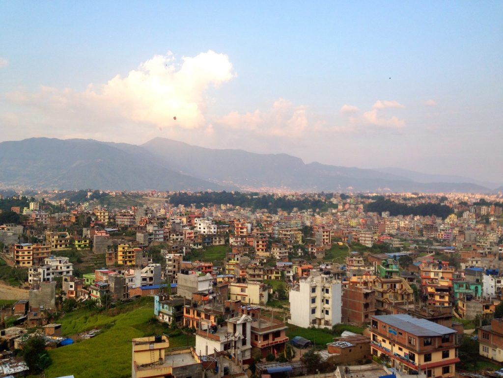 A view of Kathmandu from above, crowded houses painted different colors.