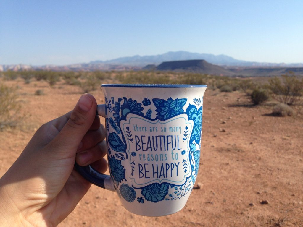 Having a cup of coffee with a desert backdrop.