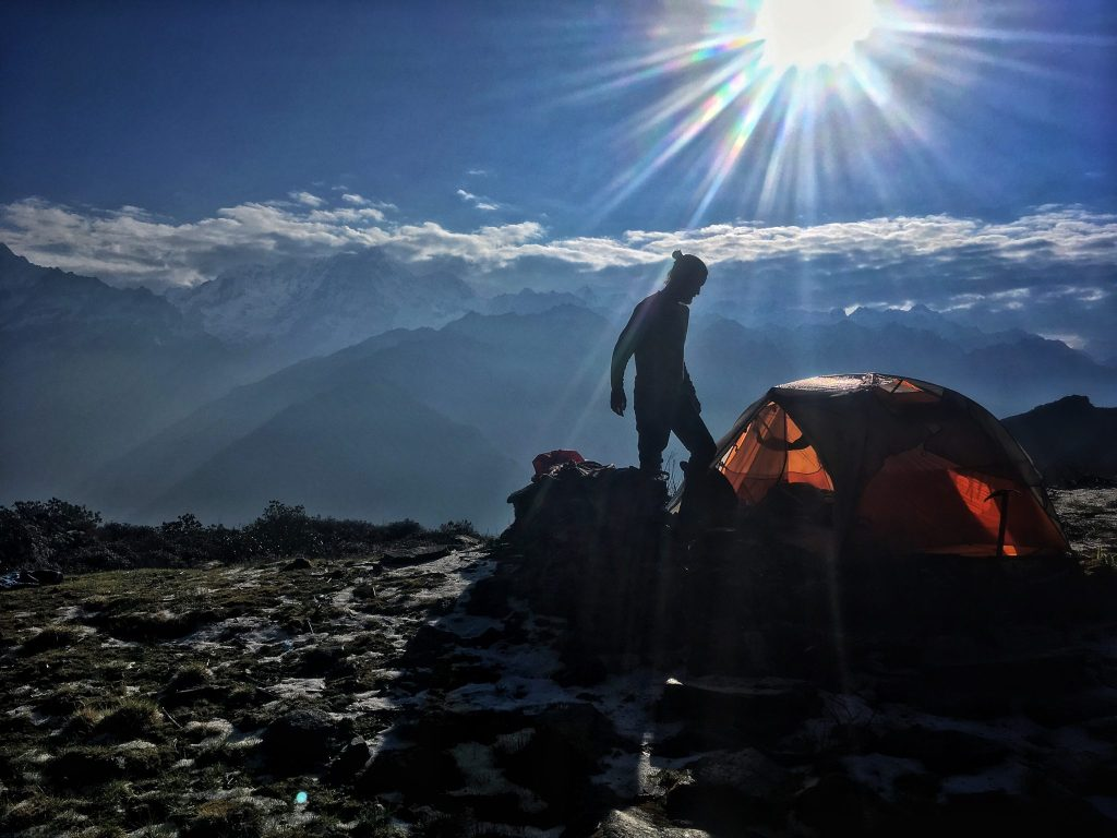 A hiker in front of his tent with the sun shining and the Himalaya mountains.