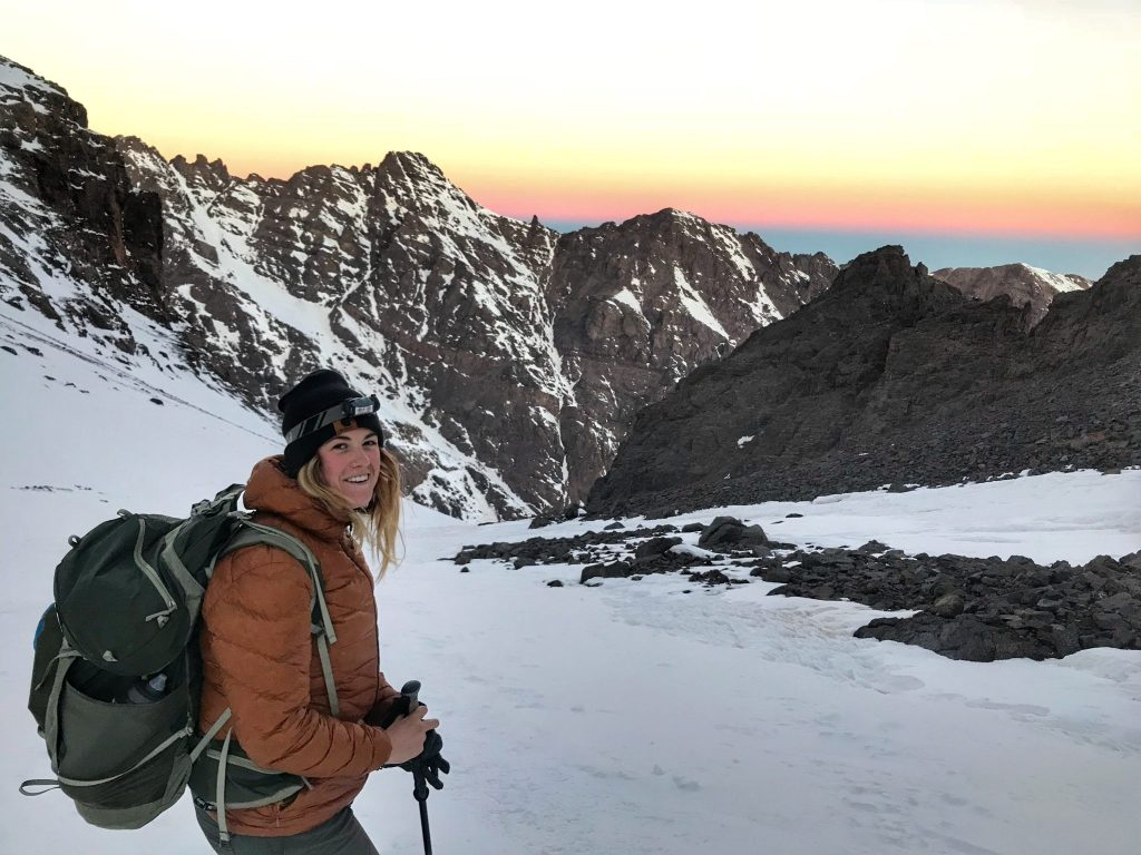 Female hiker standing in the snow smiling during sunrise on Mount Toubkal.