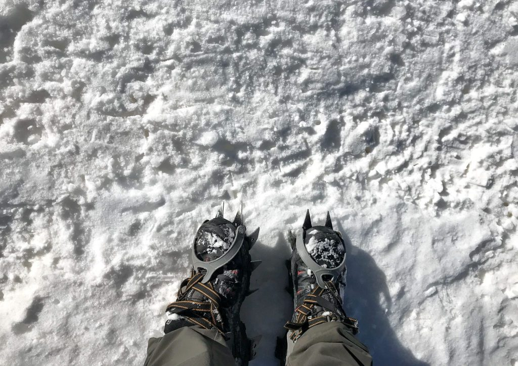 Shoes with crampons on standing in the snow.