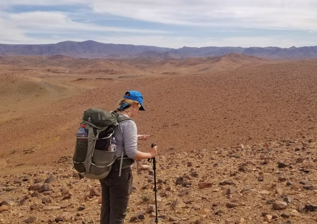 Hiker in the desert looks at a compass.