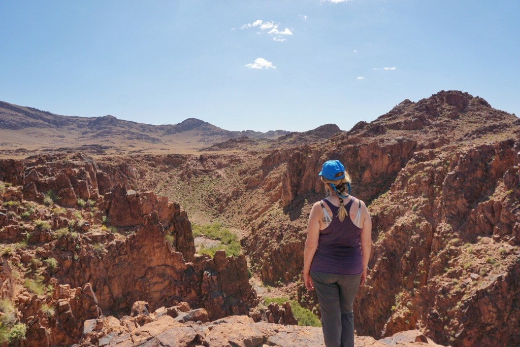 A hiker looking out into a canyon in Morocco's desert.