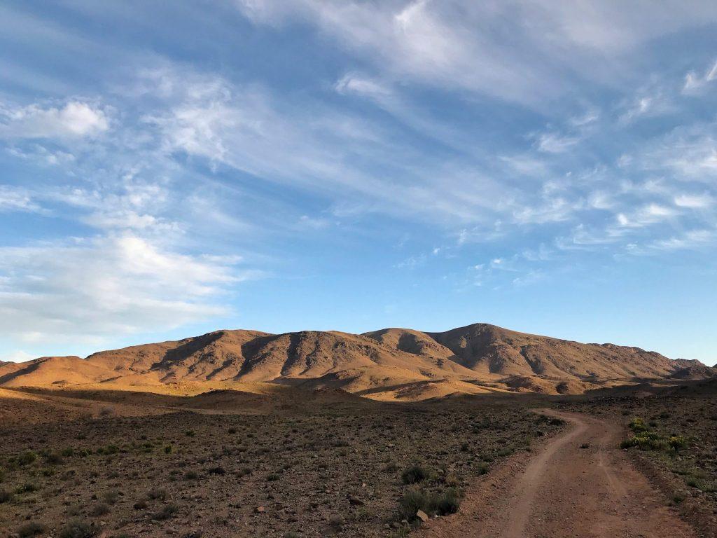 A dirt road winds toward a mountain.