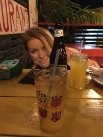 Mandy hiding behind beverages in Caye Caulker Belize
