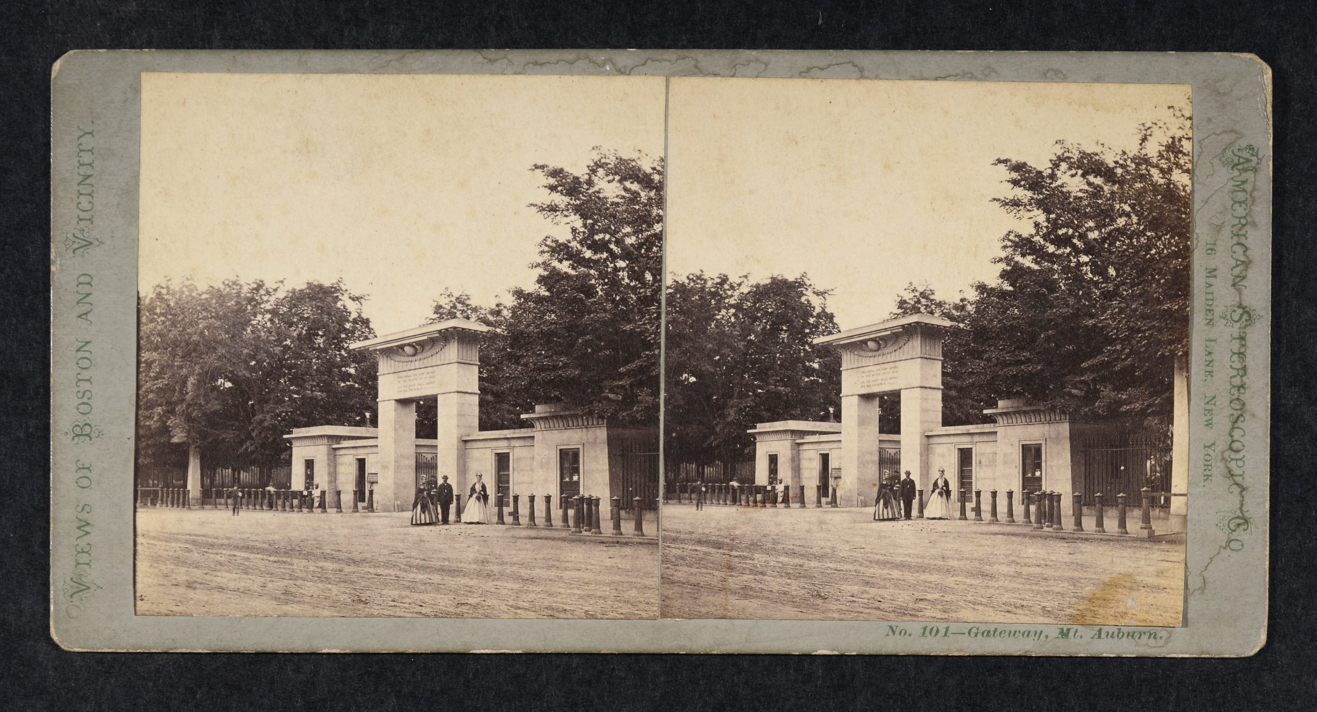 Stereoview of dirt road, Egyptian Revival entrance Gateway, 2 women and 1 man in front.