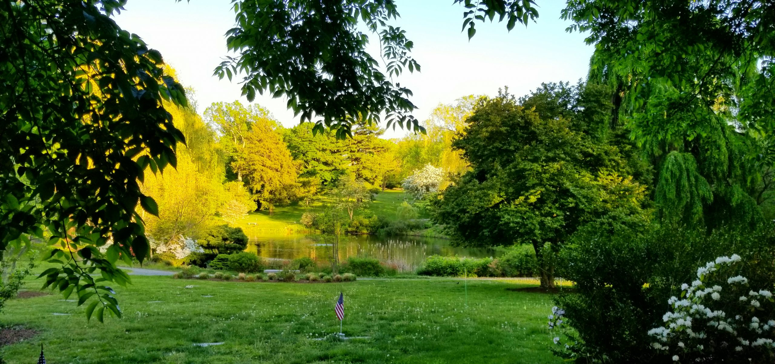 A grassy lawn sloping down towards a pond. Monuments are flush with the grass to preserve the view of the pond.