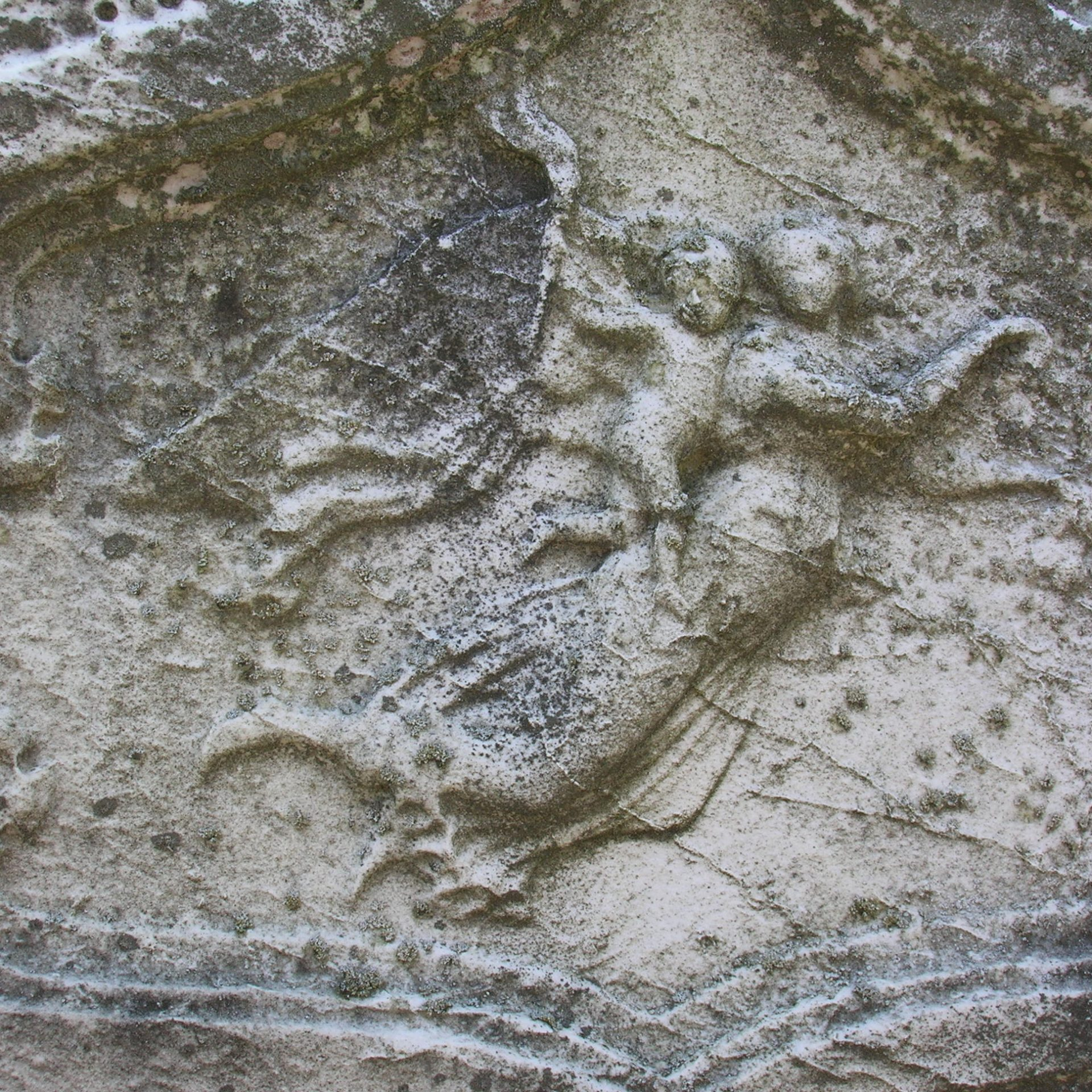 Detail of a weathered marble monument. The image of an angel carrying an infant (to heaven) is severely weathered, but still recognizable.