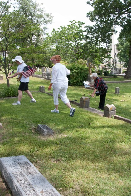 Volunteers fan out across the grounds to find the graves of veterans.