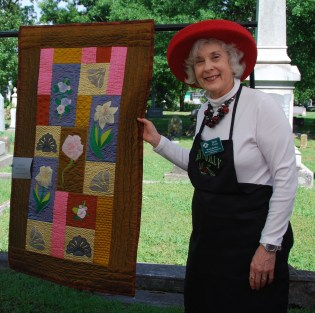 Picnic co-organizer and Association member Judy Goss stands next to the silk Mount Holly quilt, created from tombstone iconography and motifs in the cemetery. The quilt was designed and made by Lavern Schaap and donated for the 2017 auction.