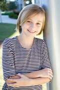 Sarah, celebrating her 12th birthday during our photo shoot, wears a tan and brown striped, three-quarter-sleeve dress from Blush.