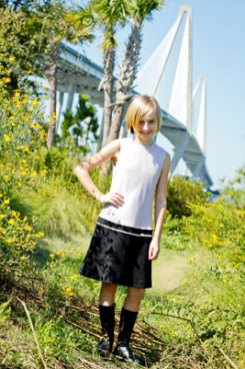 Sarah (12) poses with the Arthur Ravenel Bridge as a backdrop while wearing a sleeveless white and black knee length dress from Blush with knee high socks and black loafers. This outfit is perfect for adding or taking away layers throughout the fall.