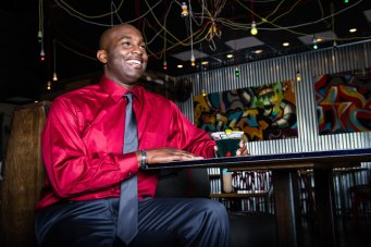 Jermaine looks smashing and ready for the holidays in this eye catching red, button down Van Heusen shirt and dark gray Madison tie provided by Belk in Mount Pleasant Towne Center. He enjoys a drink in the laid back atmosphere at Triangle Char & Bar.