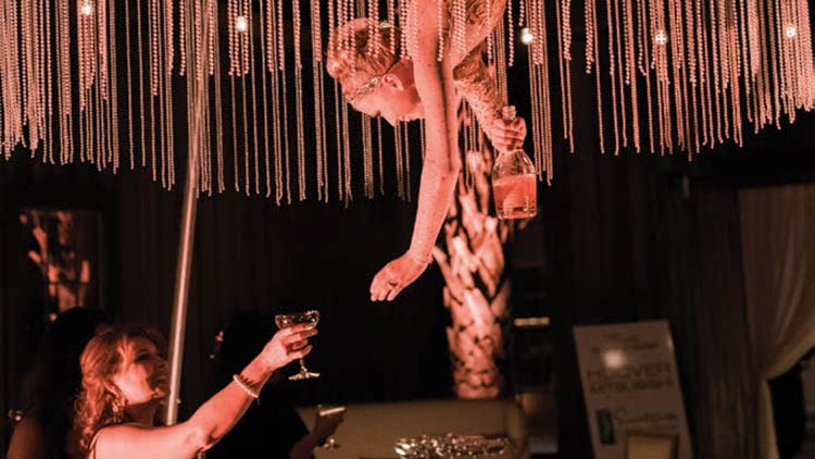 An aerialist pours bubbly at Uncorked.