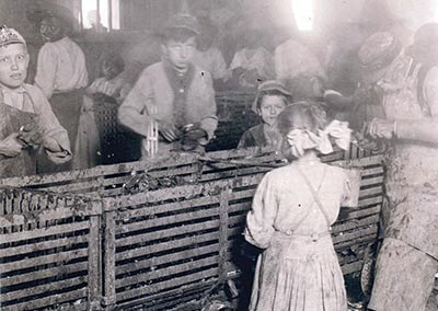 A group of children shuck oysters.