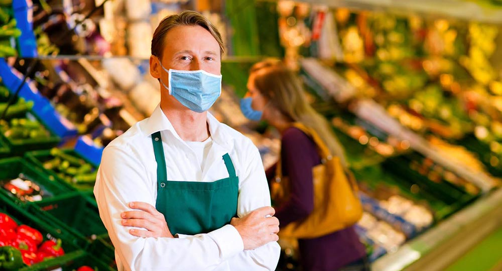 A grocery store employee with a shopper in the background