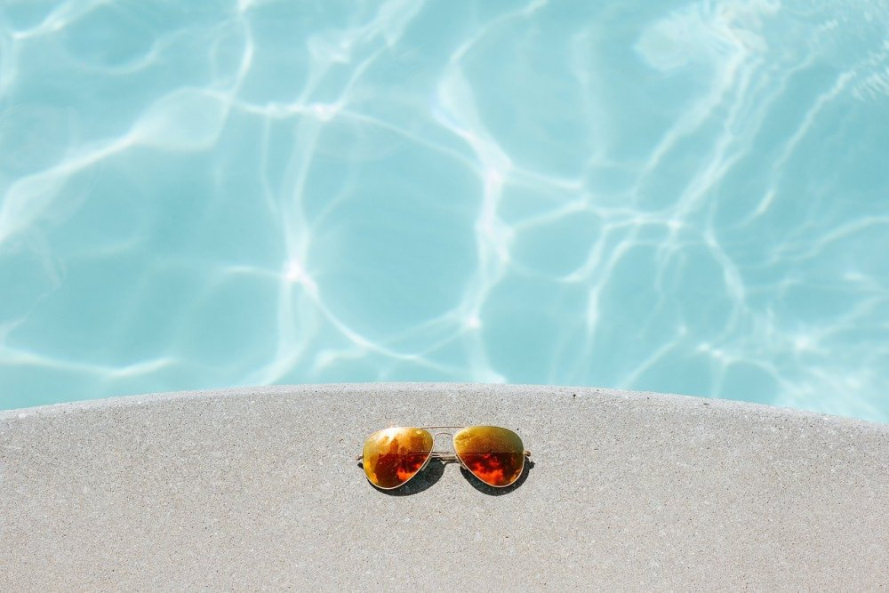 Photo of a swimming pool with sunglasses on the side. (photo by Pexels from Pixabay)