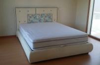 Cama com cabeceira com diferentes tecidos com aplicação de botões estofados.Fabricamos camas estofadas por medida.