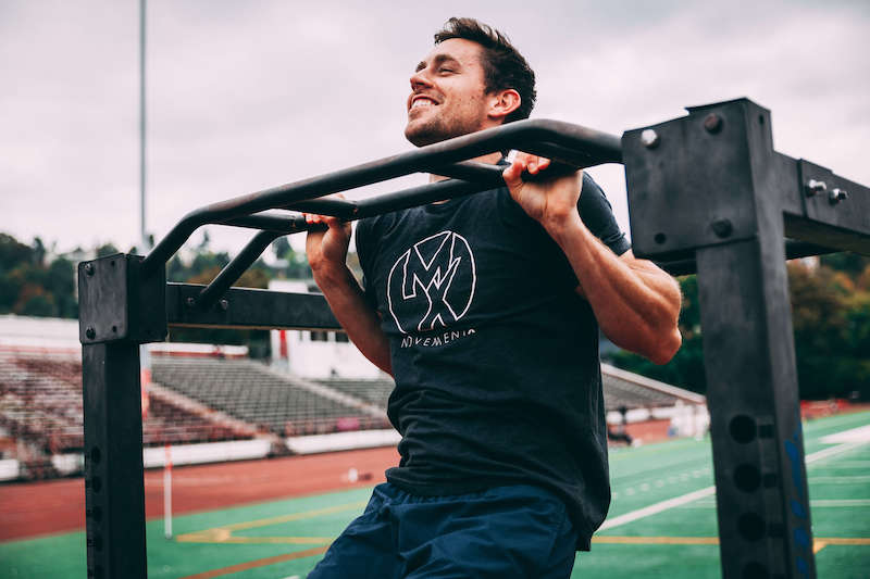 Man in a MovementX shirt doing pullups