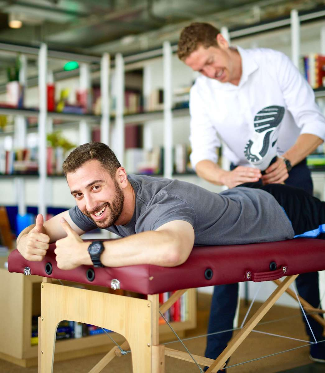 Physical therapist stretching man's quads in his workplace