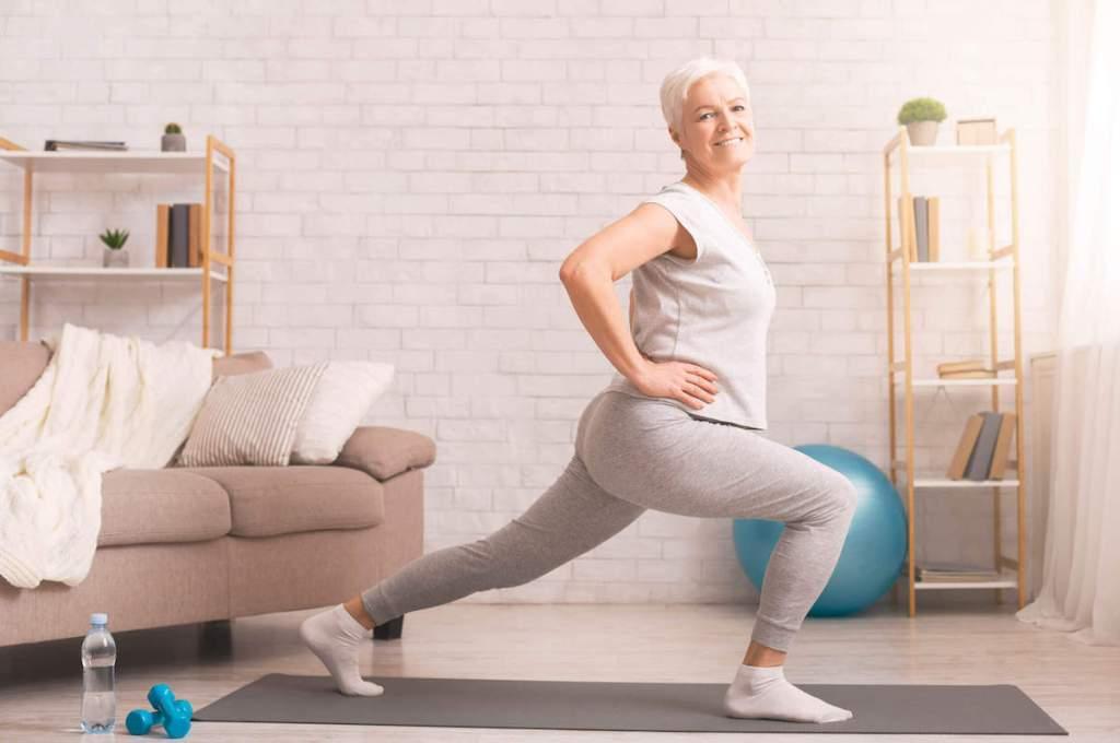 Older woman exercising in a lunge position in home