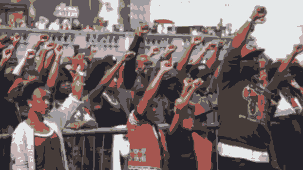 A crowd of people with their fists raised.