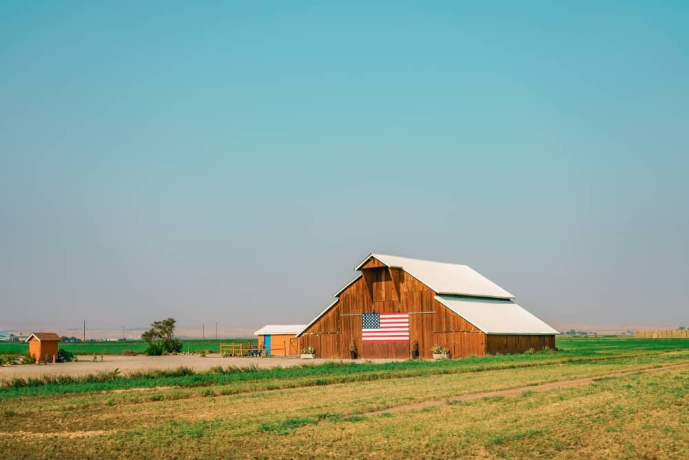 A barn in the middle of a field with a US flag on the side.